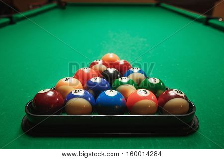 Two cues and pyramid on a billiard table.