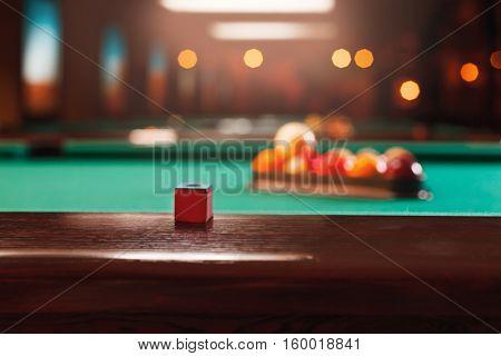 Chalk on the edge of the billiard table.