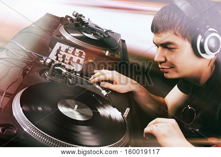 Club DJ playing mixing music on vinyl turntable at party wearing sunglasses with lens flare from nightlife lights