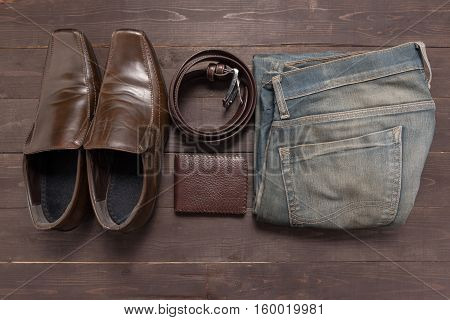 Elegant Set: Brown Wallet, Brown Men's Shoes, Brown Leather Belt, Jean On The Wooden Background