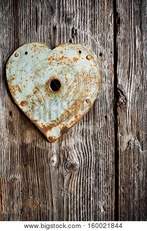 Rusty old trim on keyhole in shape of heart on old wooden door. Vertical shot.
