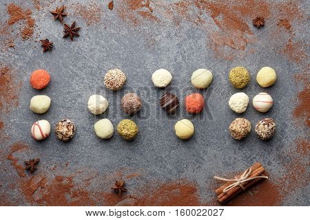 Various chocolate truffle candies arranged in a word love on gray stone background