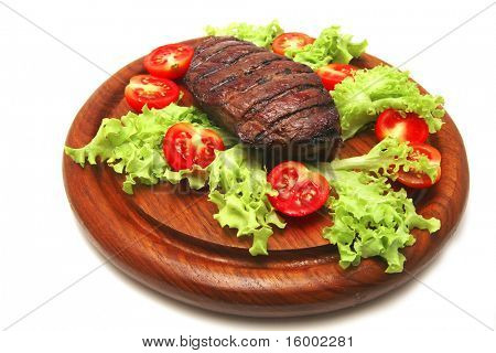 served roasted beef meat steak on wooden plate