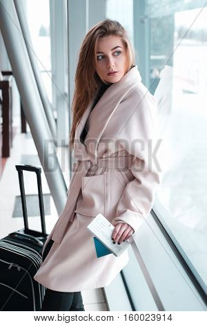 Businesswoman with baggage poses at the airport.