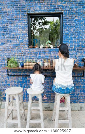 Mother and kid sitting on the chair with blue wall Where is daddy?