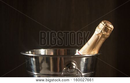 Bottle of Champagne in bucket on black background