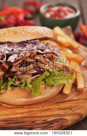 Pulled pork sandwich with lettuce and coleslaw salad