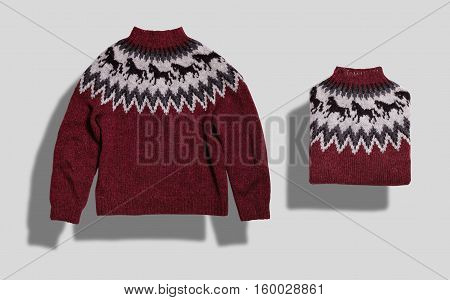 Red, white and navy fairisle woolen knitted sweater lying flat and folded neatly isolated on white