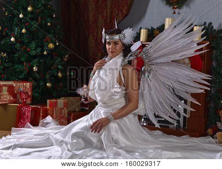 Woman in white angel costume near Christmas tree