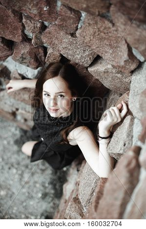 Beautiful Sad Young Woman On A Stone Wall Background