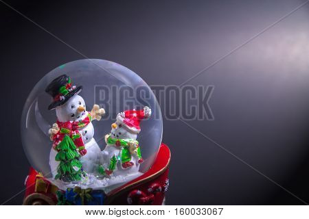 Christmas snow globe with snowman isolated on black background