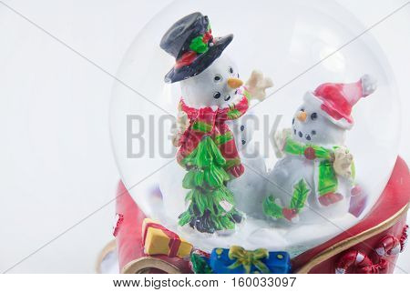 Close-up Christmas snow globe with snowman isolated on white background