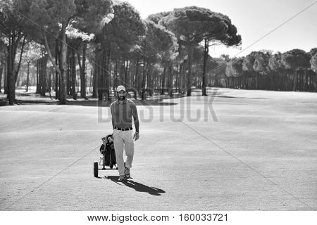 handsome middle eastern golf player carrying and bag and walking at course on beautiful sunset