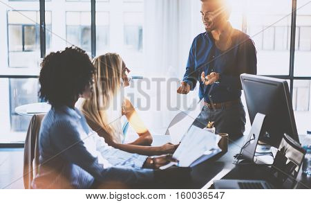Young team of coworkers making great meeting discussion in modern coworking office.Hispanic businessman talking with two beautiful womans.Teamwork process.Horizontal, blurred background, flares effect