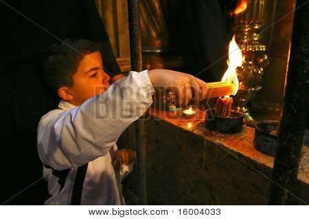 JERUSALEM - APRIL 17: Little boy kindle candles at Holy Sepulchre for Holy Fire (Holy Light) miracle ceremony on Holy Saturday Apr 17, 2009 in Jerusalem. About 10,000 worshipers attended the ceremony.