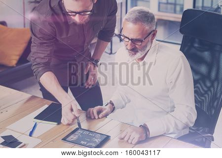Young team of coworkers found a great work solution in modern coworking studio.Bearded man showing statistic repot, graph and diagramm on digital tablet.Business people brainstorm concept.Flare effect