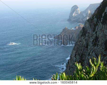 Desolate atlantic rocky coast of CABO DA ROCA (CAPE ROCA) with grass, westernmost extent of mainland continental Europe with clear sky in cold autumn day, PORTUGAL, OCTOBER 2016.