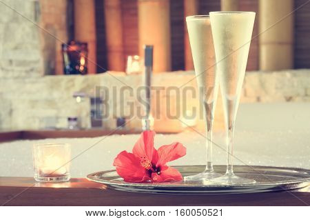 Two Glasses Of Champagne With Candle And Red Flower Near Jacuzzi. Valentines Background. Romance Con