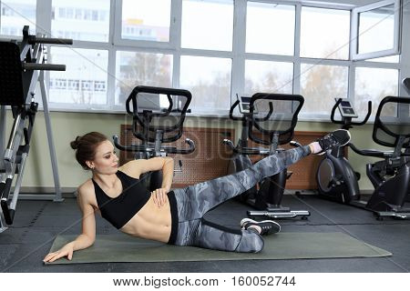 Girl doing exercises aerobics warming up with gymnastics for flexibility leg up stretching workout at gym fitness