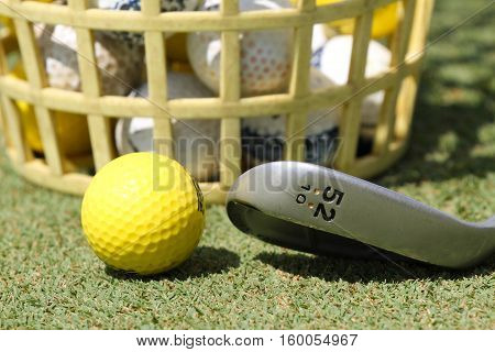 Macro shot of practice golf ball in a bucket and a golf iron on the practice green