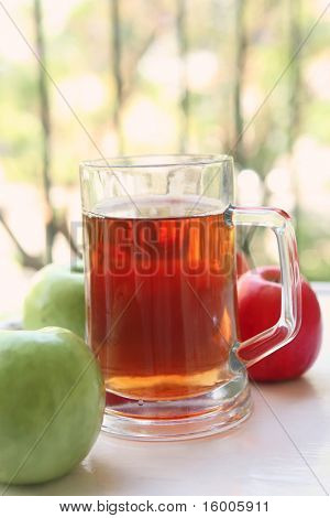 apple juice inside big glass with raw apples