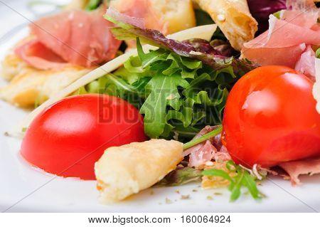 Salad with prosciutto, parmigiano, fresh cherry tomato, lettuce and ruccola