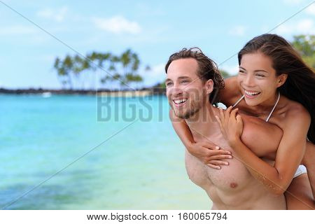 Beautiful healthy young people having fun. Multiracial piggyback couple on beach travel vacation in Caribbean destination. Happy smiling man piggybacking Asian woman.