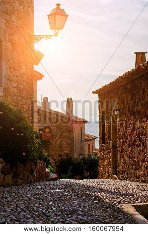 Beautiful view of scenic narrow alley street with historic traditional houses in an old town in Europe with blue sky and clouds in summer sunny day with retro vintage Instagram warm filter effect