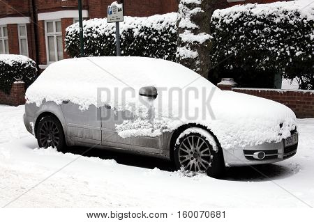 London, UK, December, 19 2010: A heavy snow fall covering a car in a Kilburn street bringing transport to a standstill