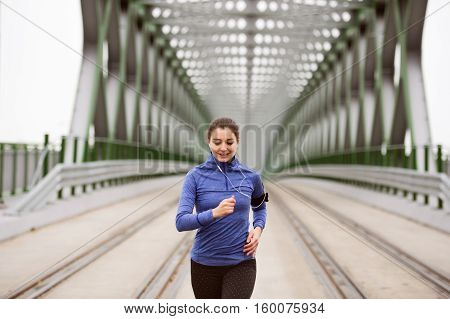 Beautiful young woman with smart phone and earphones, listening music, running in the city on green steel bridge.