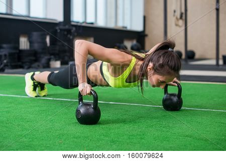 Fit woman young doing push ups exercise with dumbbells in the gym.