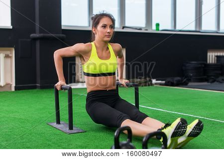 fit strong woman doing L-sits work-out in gym, lifting up her legs, using parallel bars.
