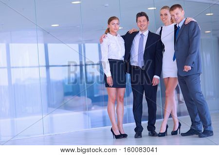 Young businessmen and woman in classic clothes standing near the office building
