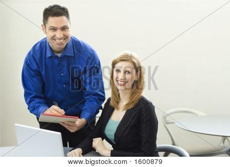 Sonrisa de trabajadores cerca de escritorio