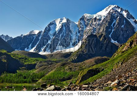 The top of the mountain covered with glaciers flowing down to the rocky slope. Altai, North-Chuya ridge - Highlands region of Siberia. Lake Shavla and peaks reflecting in the water
