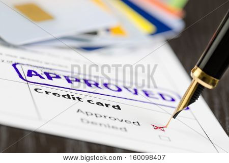 Credit card form close up fountain pen and approved stamped on a document.
