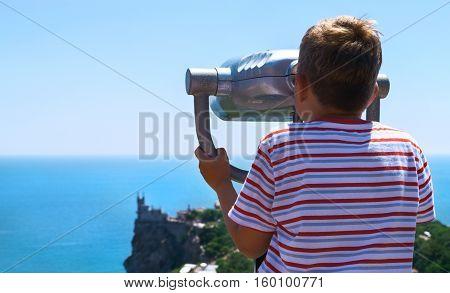 boy looking in binoculars on an observation castle Swallow's Nest