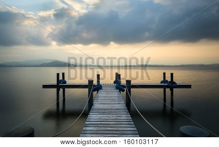 Wooden pier on the lake Zug Switzerland. Fog. Sunset in pastel colors. Long exposure.
