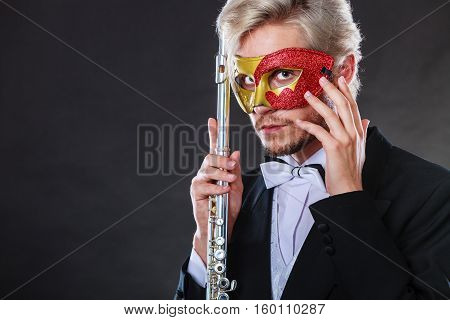 Holidays people and celebration concept. Elegant young guy wearing suit white shirt bow tie and carnival venetian mask holding flute instrument on dark