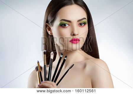 Young Beautiful Girl With Bright Makeup. A Woman Holds A Professional Makeup Brushes