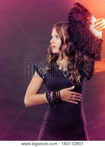 Portrait of beautiful brunette woman with black feather fan in hand on festive colorful background