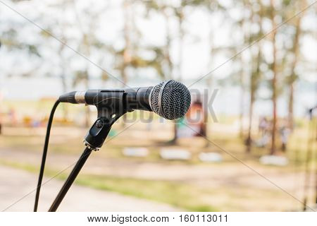 A microphone on stage. The concept of a concert in the open air.