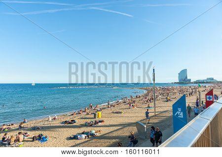 Barcelona, Spain - September 17, 2016; Barcelonetta Beach with architecturally modern W Hotel in distance sunbathers along sandy beach Barcelona Spain