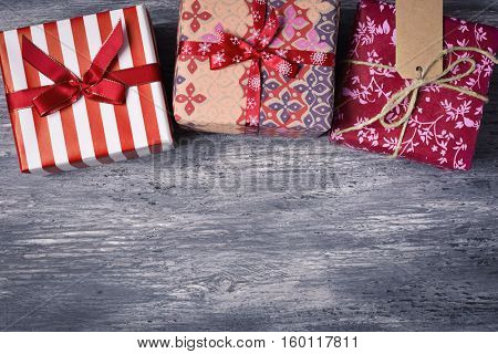 high-angle shot of some cozy gifts wrapped in different nice papers and tied with ribbons and strings of different colors on a rustic wooden surface, with a negative space