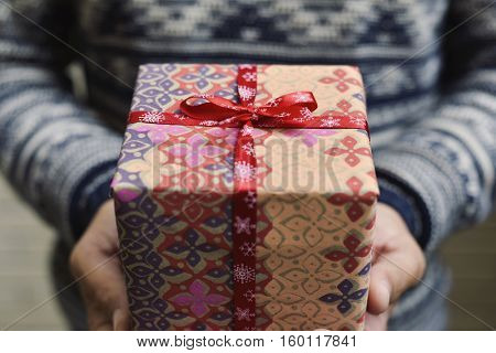 closeup of a young caucasian man wearing mittens holding a cozy gift tied with red ribbon