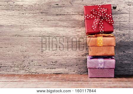 a stack of some cozy gifts wrapped in different papers and tied with ribbons of different colors on a rustic wooden surface, with a negative space