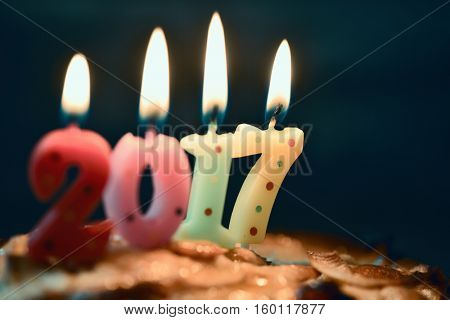 closeup of four lit number-shaped candles of different colors forming the number 2017, as the new year, on a cake