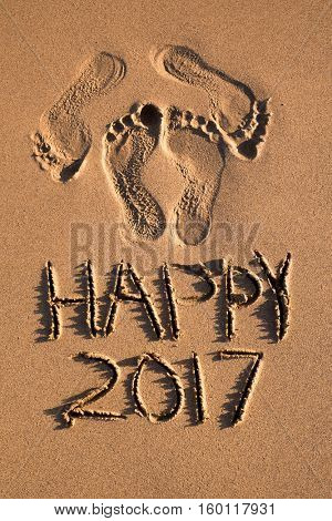some foot prints and the text happy 2017 written in the sand of a beach