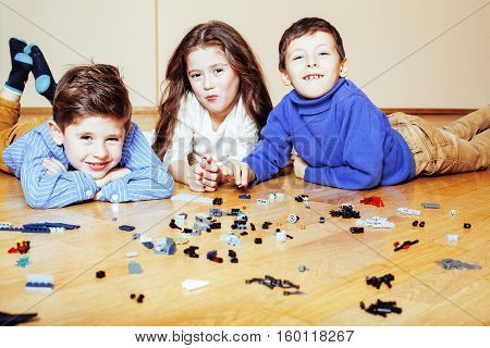 funny cute children playing lego at home, boys and girl smiling, first education role lifestyle close up