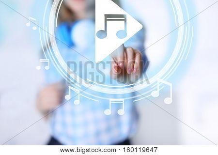 Woman pushing PLAY button on virtual screen to launch music player, closeup